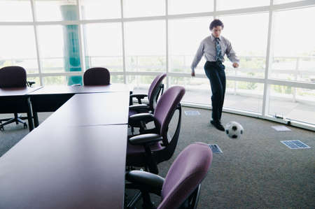 french ethnicity: Businessman playing football in an office