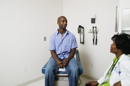 Female doctor talking to a mid adult male patient