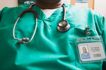 soundness: Male doctor sitting on a chair wearing scrubs