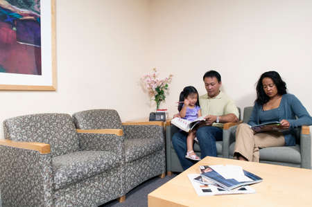 Young couple and a young girl sitting in a waiting room