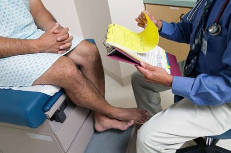 two persons only: Male patient sitting on an examination table in a doctors office LANG_EVOIMAGES