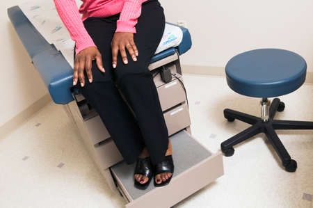 low section view: Low section view of a mature adult female patient sitting on an examination table