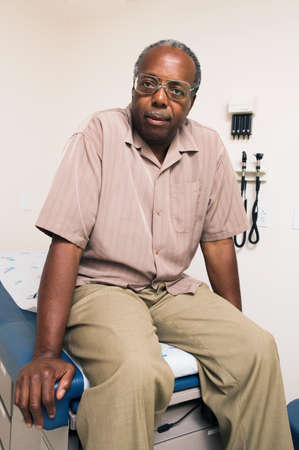 rewarding: Portrait of a mature adult male patient sitting on an examination table