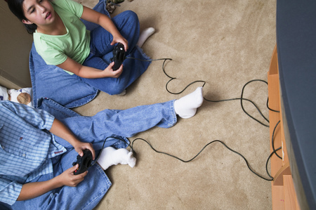 Young girl and a young boy playing a video game