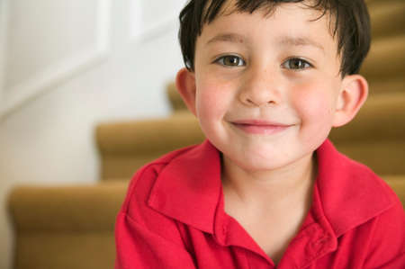 living being: Portrait of a young boy sitting on stairs smiling