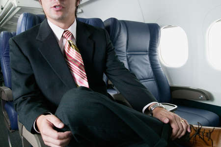 xerox: Mid adult businessman traveling in an plane LANG_EVOIMAGES
