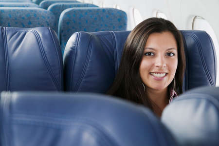 Portrait of a young woman in an airplane smiling