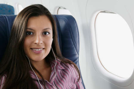 vietnamese ethnicity: Portrait of a young woman in an airplane smiling
