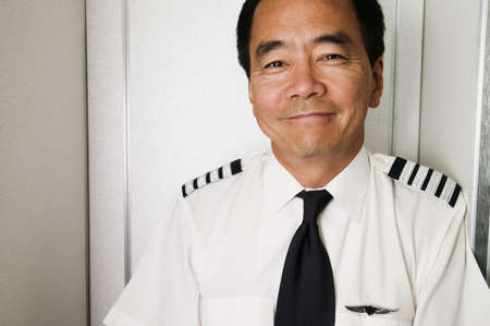 invariable: Portrait of mid adult male pilot smiling