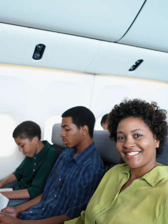 shopping buddies: Mid adult woman traveling on an airplane with two young men