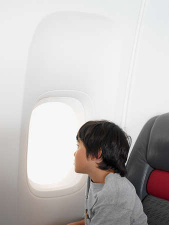 Young boy looking out a window in an airplane LANG_EVOIMAGES