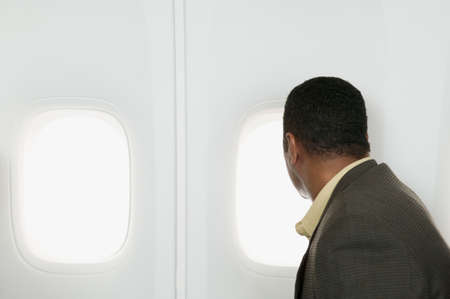 Side profile of a businessman looking out a window in an airplane