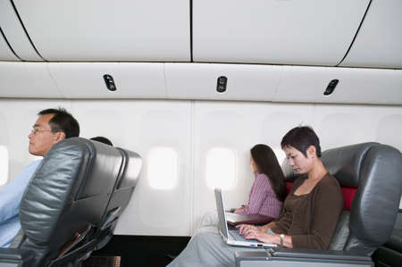vietnamese ethnicity: Mid adult woman sitting in an airplane working on a laptop