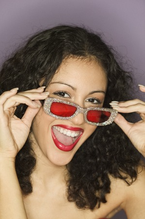 Young woman wearing sun glasses looking at camera smiling