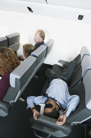 High angle view of a businessman sleeping in an airplane Stock fotó