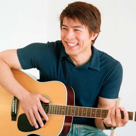 topsyturvy: Young man playing a guitar