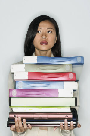 Teenage girl standing holding a stack of files