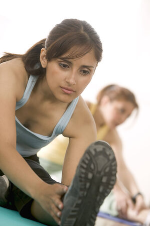 two persons only: Young women exercising in a gymnasium LANG_EVOIMAGES
