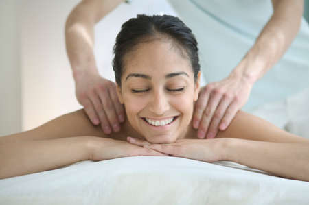 three persons only: Young women getting a back massage smiling LANG_EVOIMAGES