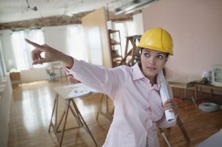 freewill: Mid adult woman wearing a hardhat pointing up