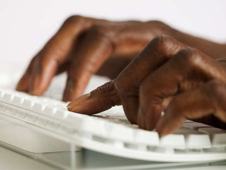 way of behaving: Close-up of a mans hands working on a computer keyboard