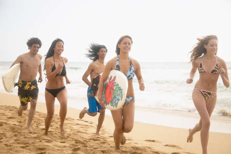 aplomb: Group of teenagers running on the beach LANG_EVOIMAGES