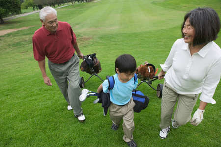 informant: High angle view of a senior couple with a young boy at the golf course
