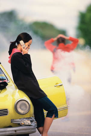 joys: Young woman leaning against a car talking on a mobile phone LANG_EVOIMAGES
