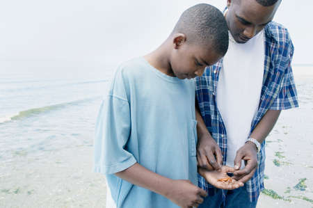 way of behaving: Father and his son collecting shells on the beach LANG_EVOIMAGES