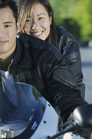 two persons only: Portrait of a young couple sitting together on a motorcycle LANG_EVOIMAGES