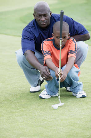 member of the clergy: Father teaching his son golf at a golf course