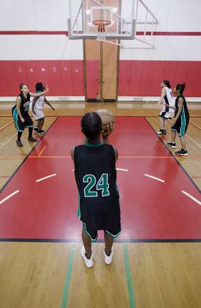 ultimatum: Team of female teenage basketball players playing basketball on a basketball court