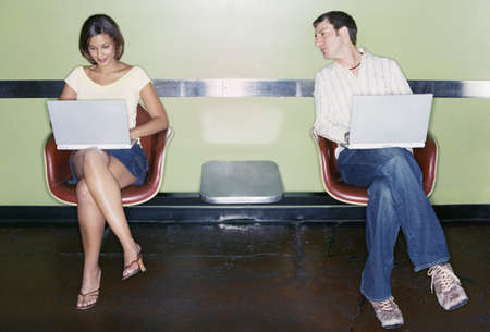 Young couple sitting working on laptops