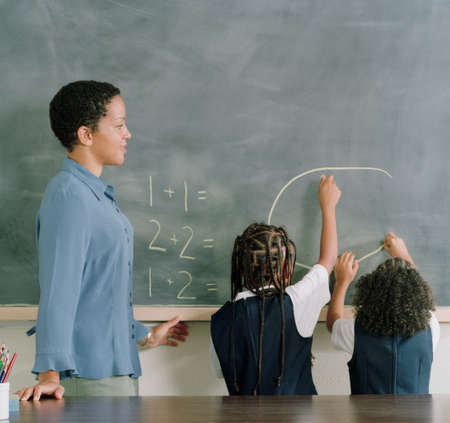 arousing: Young female teacher standing with two children writing on a chalk board