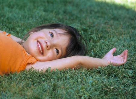 restfulness: Young girl lying on a lawn smiling