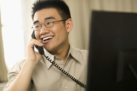living being: Young man talking on a phone smiling