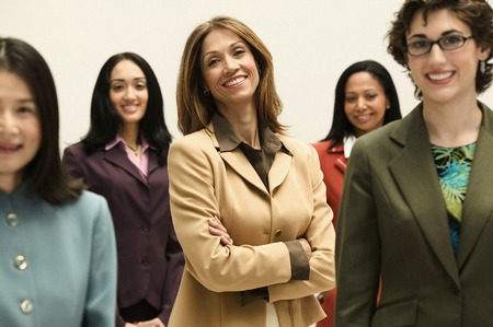 Group of young businesswomen standing together looking at camera smiling