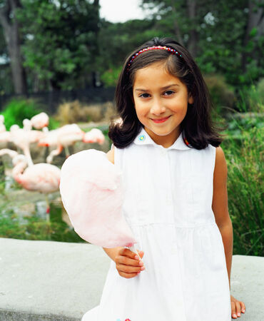 blase: Portrait of a young girl standing holding a stick of cotton candy