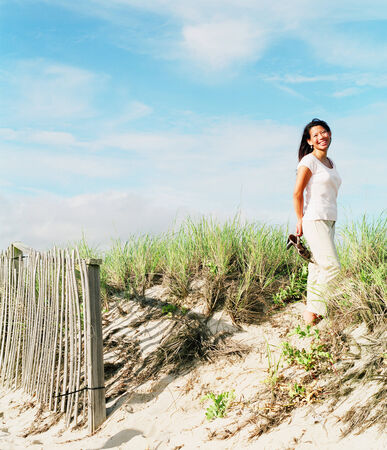 informant: Portrait of young woman standing on the beach LANG_EVOIMAGES