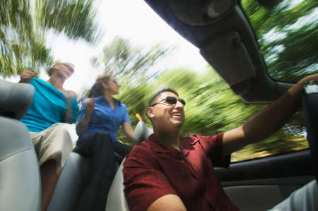 Low angle view of a young man driving a young couple in a convertible car
