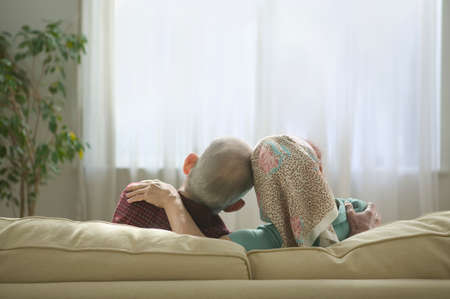 joyousness: Rear view of a senior couple sitting together on a couch
