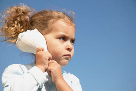 Young girl listening to a conch shell