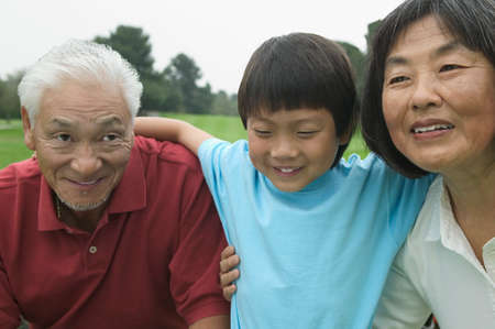 only one mid adult man: Young boy holding a senior couple LANG_EVOIMAGES