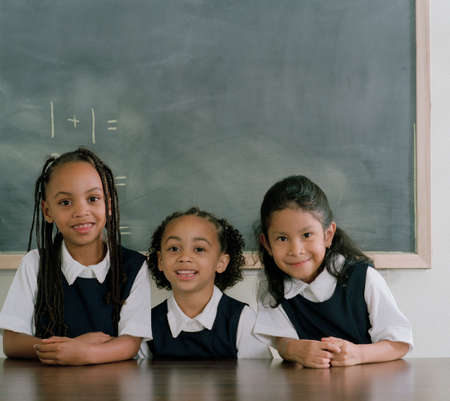 three persons only: Three young girls sitting in a classroom smiling