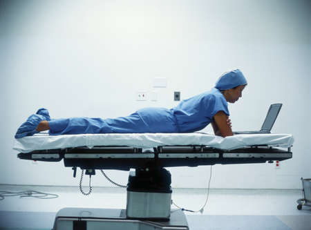 bifocals: Male nurse lying on a hospital bed working on a laptop