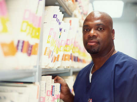 sickroom: Portrait of a male surgeon standing next to shelves of files LANG_EVOIMAGES