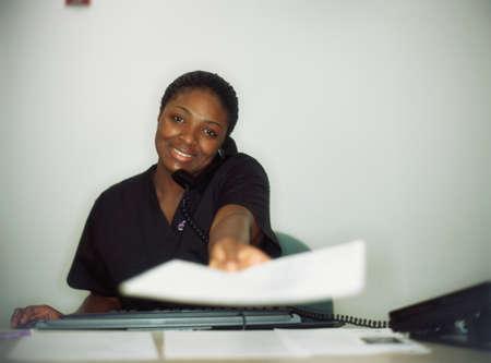 panache: Female nurse talking on a telephone holding a file