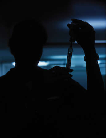 Silhouette of a nurse filling a syringe Stock Photo