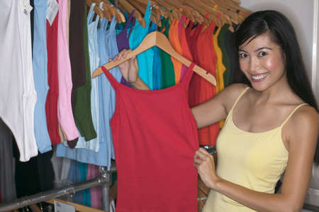 clothing rack: Woman holding a tank top in her hand LANG_EVOIMAGES