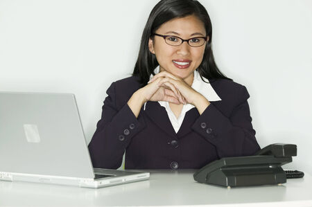 bifocals: Teenage girl sitting at a desk with a laptop looking at camera LANG_EVOIMAGES